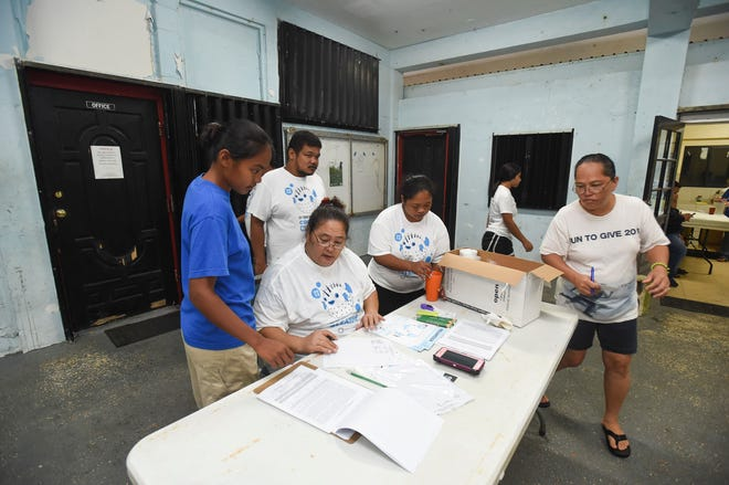 The Umatac Mayor's Office staff and volunteers organize their registration area during the 24th Guam International Coastal Cleanup at Umatac Bay on Sept. 29, 2018.