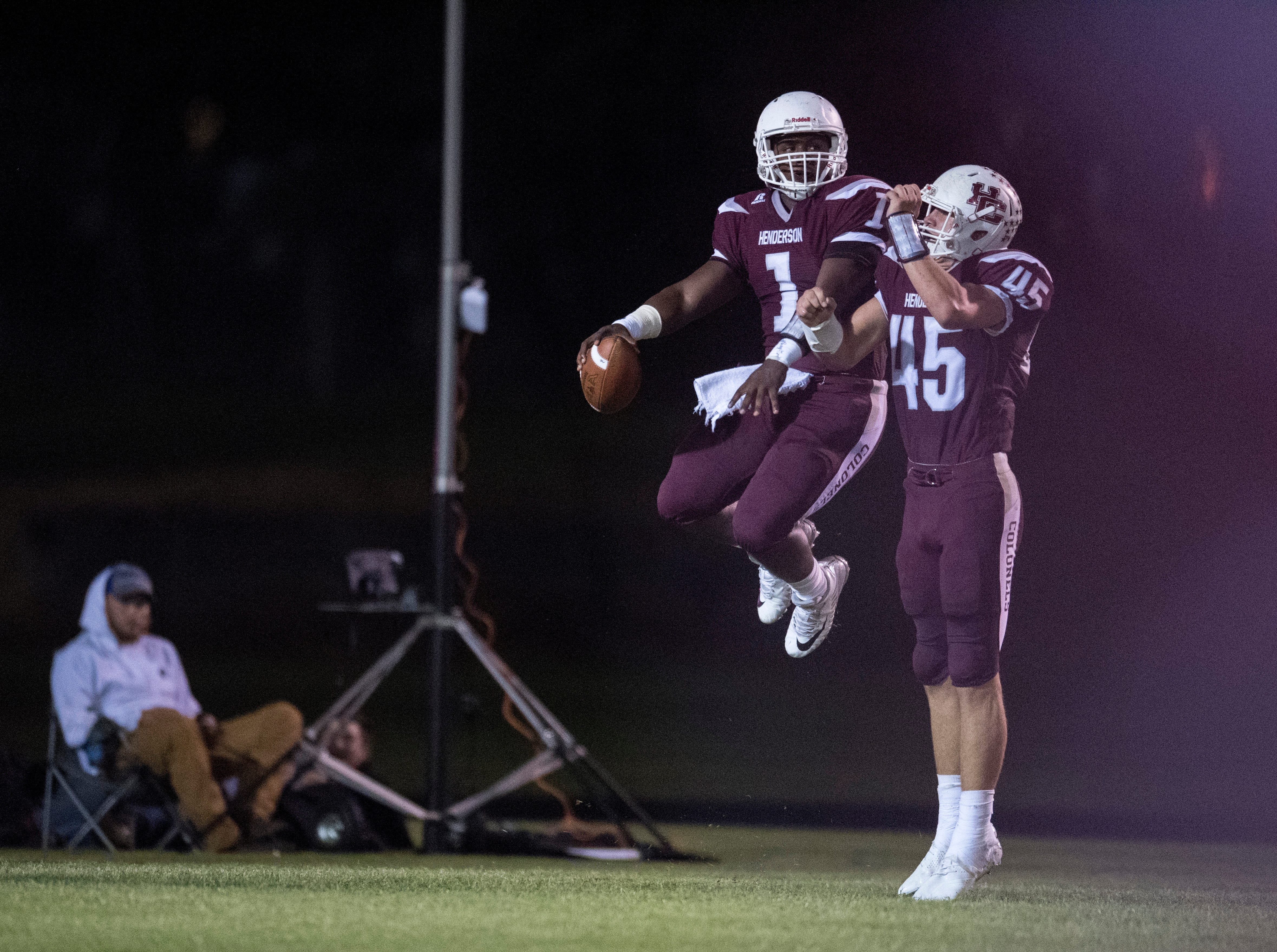 Henderson's Skip Patterson (1) and Henderson's Ian Pitt (45) celebrate after a touchdown during the Henderson vs Muhlenberg County game at Colonel Stadium Friday, Sept. 28, 2018. The Henderson County Colonels won, 61-6.