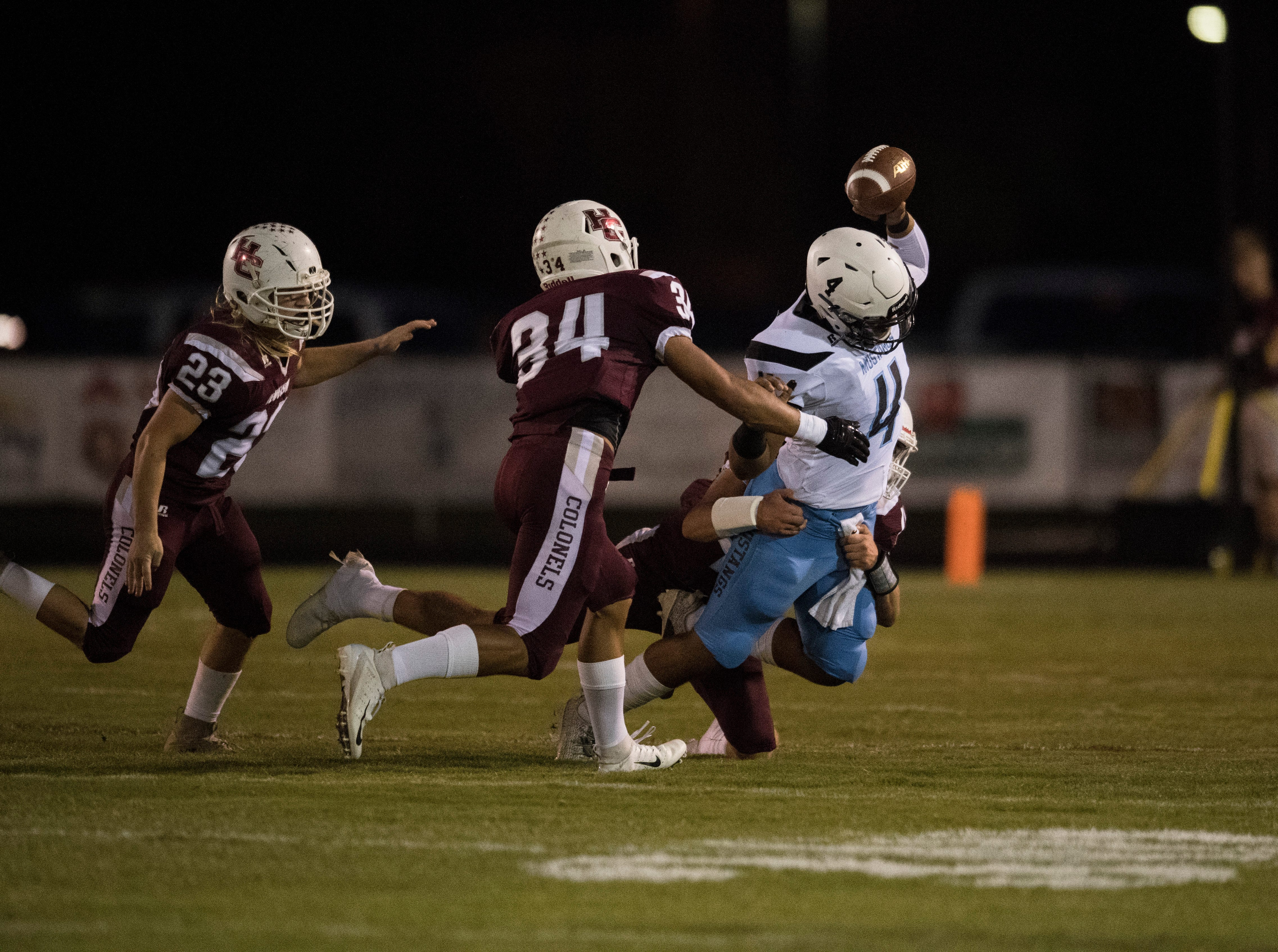 Muhlenberg County's Bronzyn Healy (4) is tackled by Henderson's Ian Pitt (45) during the Henderson vs Muhlenberg County game at Colonel Stadium Friday, Sept. 28, 2018. The Henderson County Colonels won, 61-6.