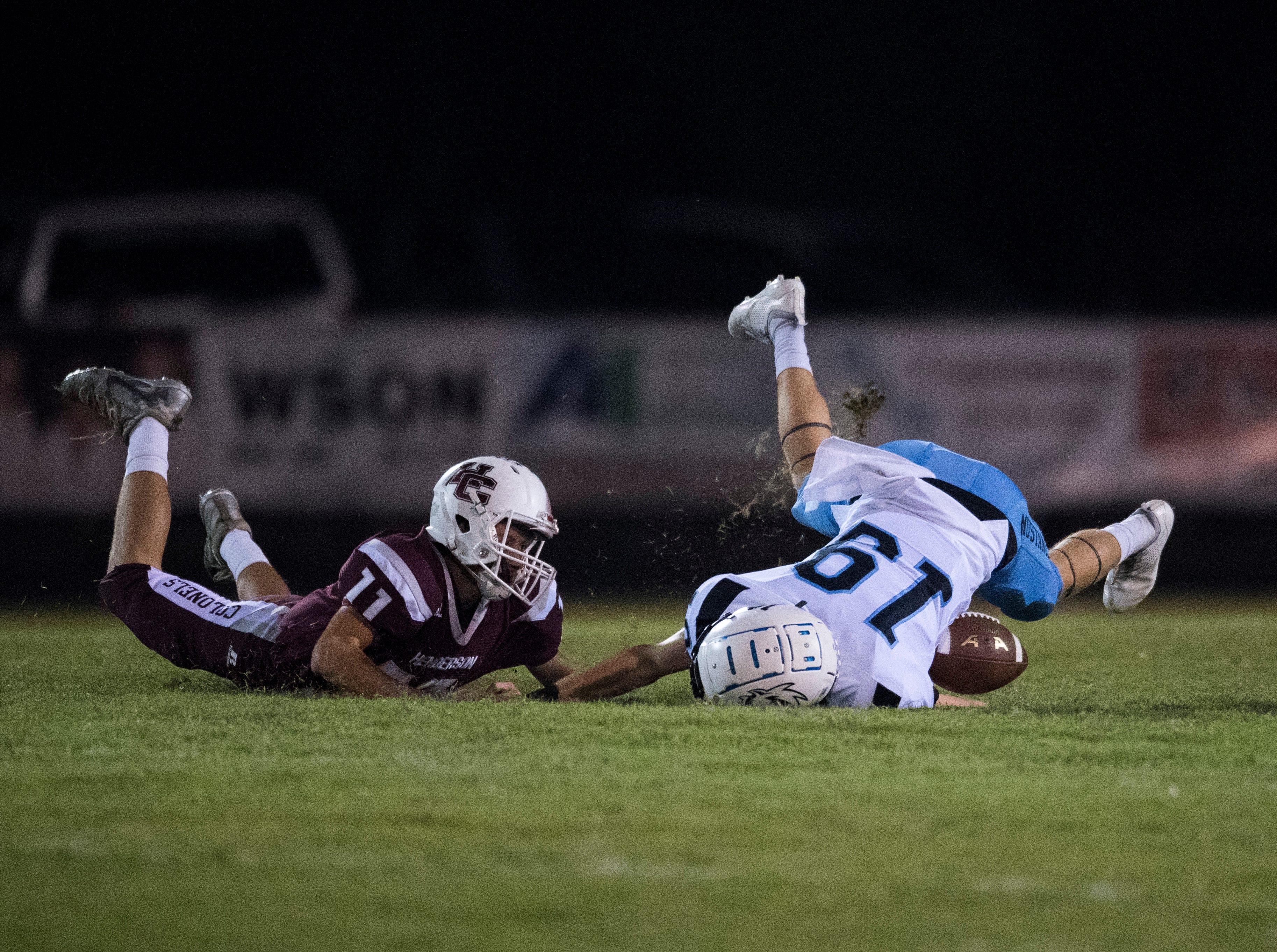 Henderson's Garrett Greenwell (11) tackles Muhlenberg County's Chris Chaney (19) during the Henderson vs Muhlenberg County game at Colonel Stadium Friday, Sept. 28, 2018. The Henderson County Colonels won, 61-6.