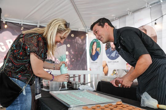 Lisa Domingo, left, learns to make macaroons from Gallery Pastry Shop owner and Executive Pastry Chef, Ben Hardy, right, during the IndyStar Wine & Food Experience, held at Clay Terrace Mall in Carmel Ind., on Saturday, Sept. 29, 2018.