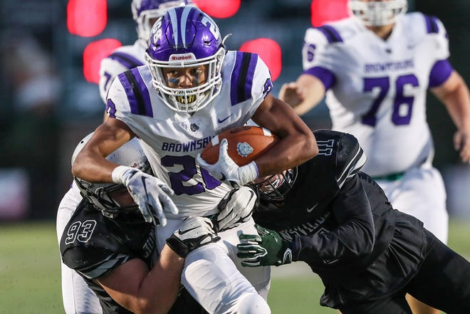 Brownsburg Bulldogs running back Donny Marcus (20) pushes through defenders near the end zone before being tackled during the first half of the game at Zionsville High School in Zionsville, Ind., Friday, Sept. 28, 2018. Brownsburg won, 70-52.