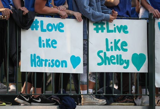 Zionsville students, fans and members of the community wear blue and display signs to remember students Shelby Hunn, 13, and Harrison Hunn, 15, during the game against Brownsburg in Zionsville, Ind., Friday, Sept. 28, 2018. The siblings were found dead in their father's home in what police are calling a double murder-suicide. Their favorite colors were blue and aqua.