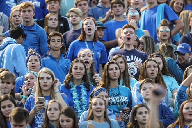 Zionsville students, fans and members of the community wear blue and display signs to remember students Shelby Hunn, 13, and Harrison Hunn, 15, during the game against Brownsburg in Zionsville, Ind., Friday, Sept. 28, 2018.