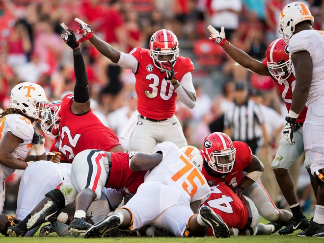 Georgia defenders motion that they recovered a fumbled ball by Tennessee running back Jeremy Banks (33) during the Tennessee Volunteers' game against Georgia in Sanford Stadium in Athens, Ga., on Saturday, Sept. 29, 2018.