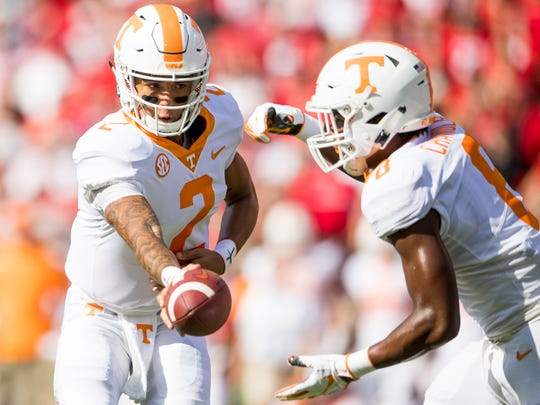 Tennessee quarterback Jarrett Guarantano (2) hands the ball off to Tennessee running back Ty Chandler (8) during the Tennessee Volunteers' game against Georgia in Sanford Stadium in Athens, Ga., on Saturday, Sept. 29, 2018.