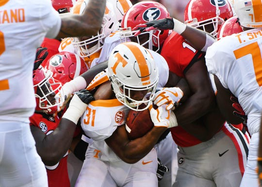 Tennessee running back Madre London (31) is stopped by several Bulldogs during first half action Saturday, September 29, 2018 at Sanford Stadium in Athens, GA.