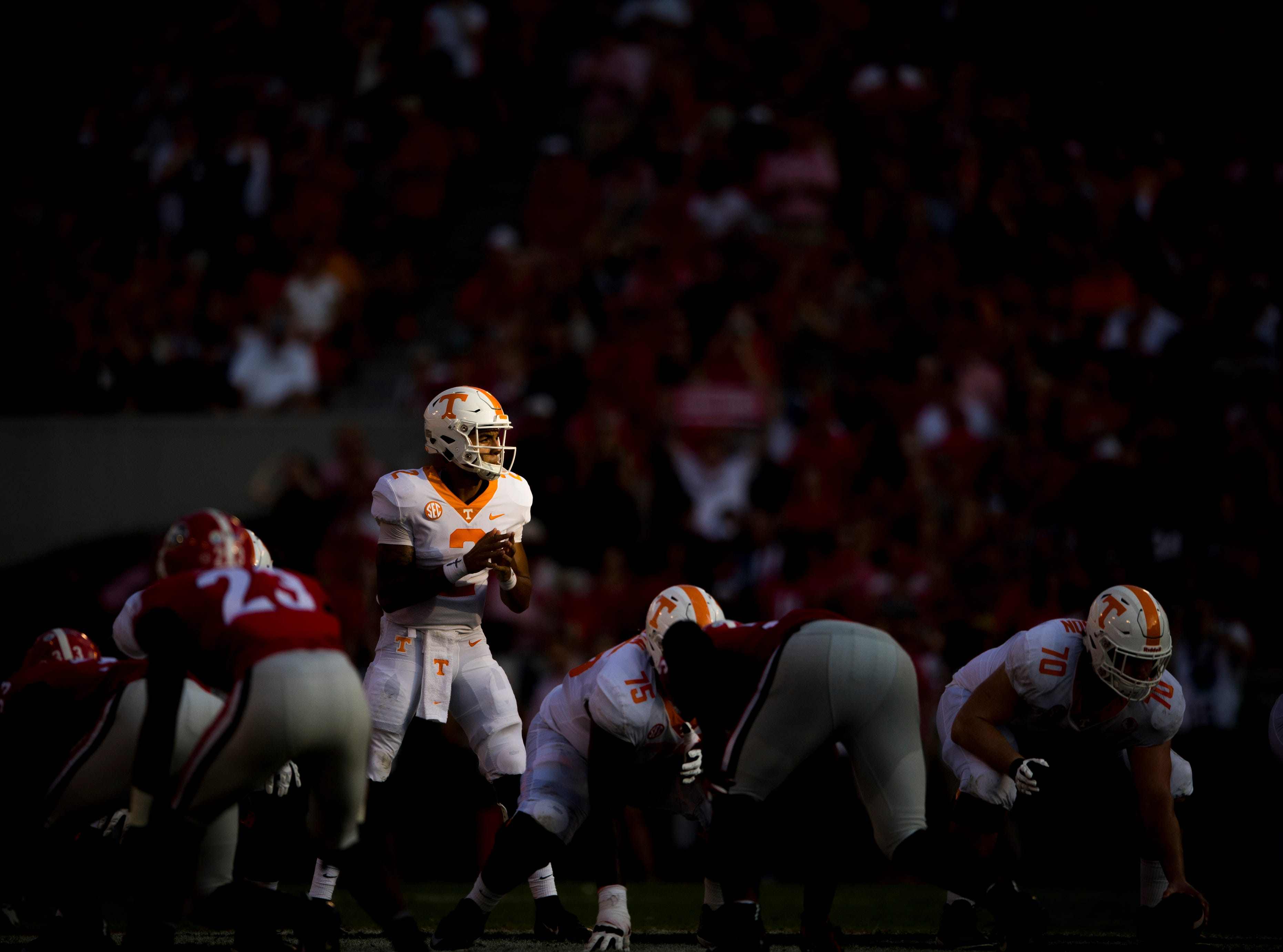 The setting sun illuminates Tennessee quarterback Jarrett Guarantano (2) as he calls for the snap during the Tennessee Volunteers' game against Georgia in Sanford Stadium in Athens, Ga., on Saturday, Sept. 29, 2018.