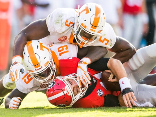 Tennessee linebacker Darrell Taylor (19) and Tennessee defensive lineman Kyle Phillips (5) take down Georgia quarterback Jake Fromm (11) during the Tennessee Volunteers' game against Georgia in Sanford Stadium in Athens, Ga., on Saturday, Sept. 29, 2018.