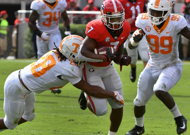 Tennessee defensive back Baylen Buchanan (28) tries to tackle Georgia running back D'Andre Swift (7) during first half action against Georgia Saturday, September 29, 2018 at Sanford Stadium in Athens, GA.