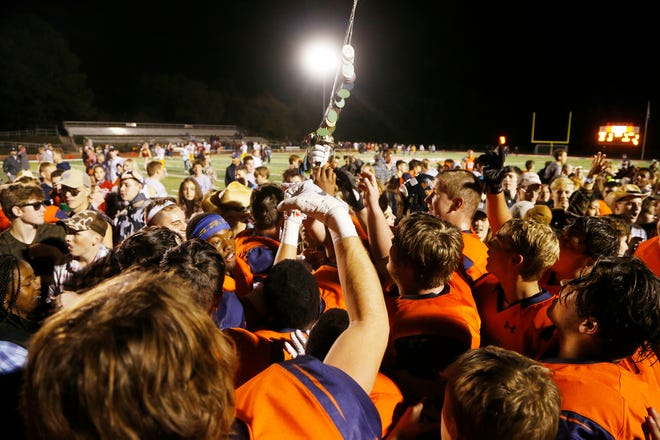Harrison players celebrate with The Sword after defeating rival McCutcheon 17-7 Friday, September 28, 2018, in West Lafayette.