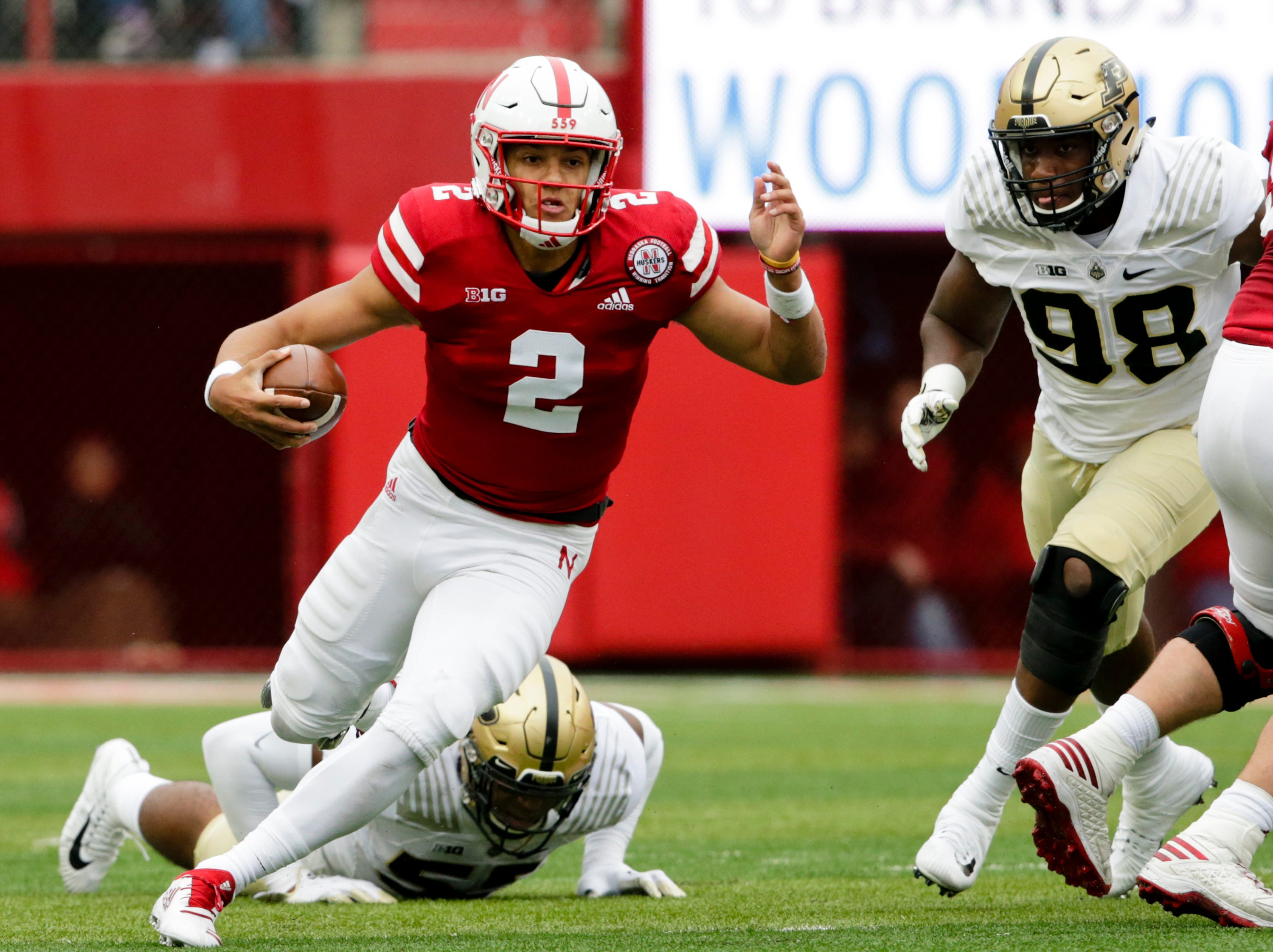Nebraska quarterback Adrian Martinez (2) carries the ball away from Purdue linebacker Derrick Barnes (55) and defensive end Kai Higgins (98) during the first half of an NCAA college football game in Lincoln, Neb., Saturday, Sept. 29, 2018. (AP Photo/Nati Harnik)