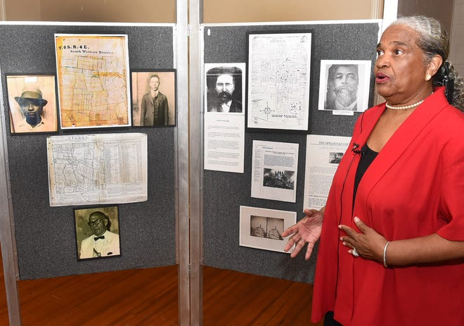 Archivist and genealogist Marie Marcel speaks before a display of historical photos at the Sept. 28 Opelousas Massacre panel discussion.