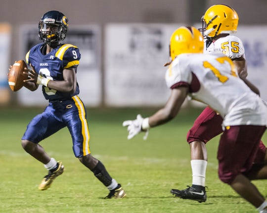 Carencro quarterback Tavion Faulk (9) rolls out of the pocket to pass the ball as the Bears play host to McDonogh 35 for Homecoming Friday Sept. 28, 2018.