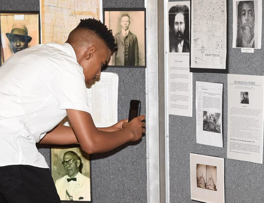 An audience member takes a picture of historical photos on the display at the Sept. 28 Opelousas Massacre panel discussion.