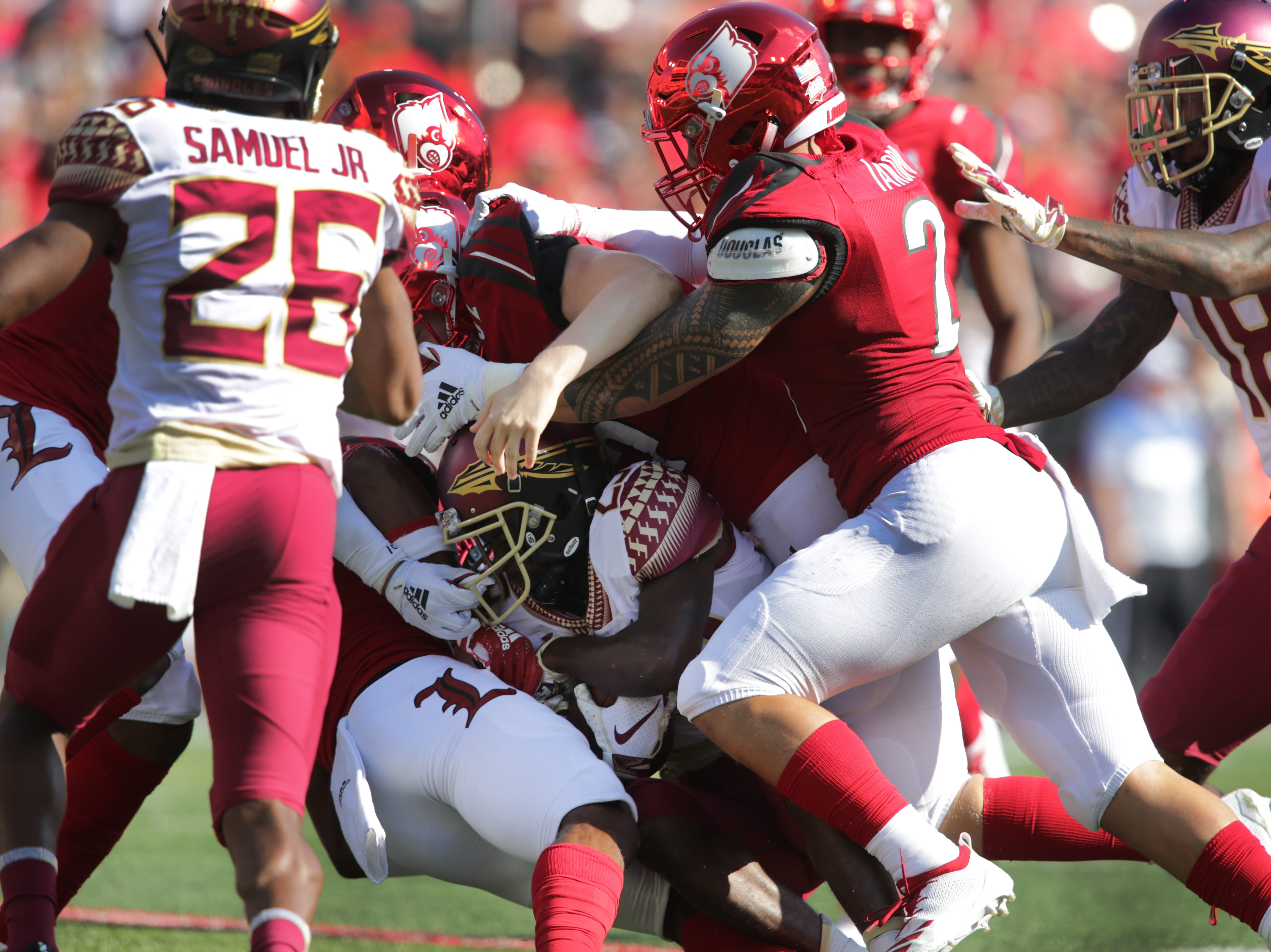 FSU's D. J. Matthews is stopped by Louisville defenders during first half action. Sept. 29, 2018.