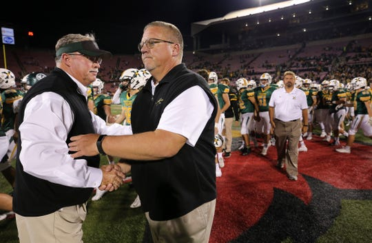 St. X head coach Kevin Wallace, right, shook hands with Trinity head coach Bob Beatty after St. X defeated Trinity 21-7 during their game at Cardinal Stadium.  