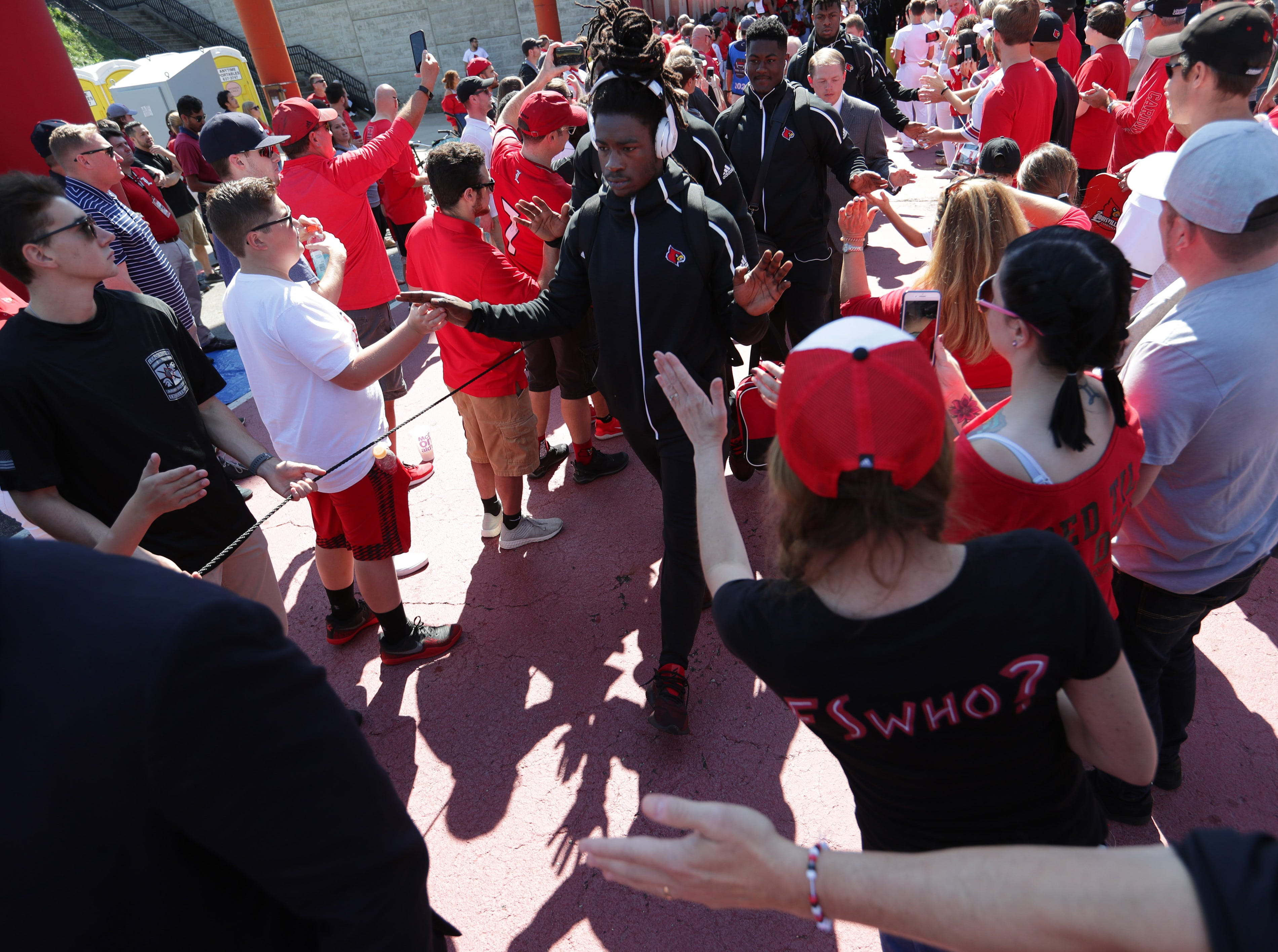 Fans reached out to University of Louisville players as they walk through the Card March. Sept. 29, 2018