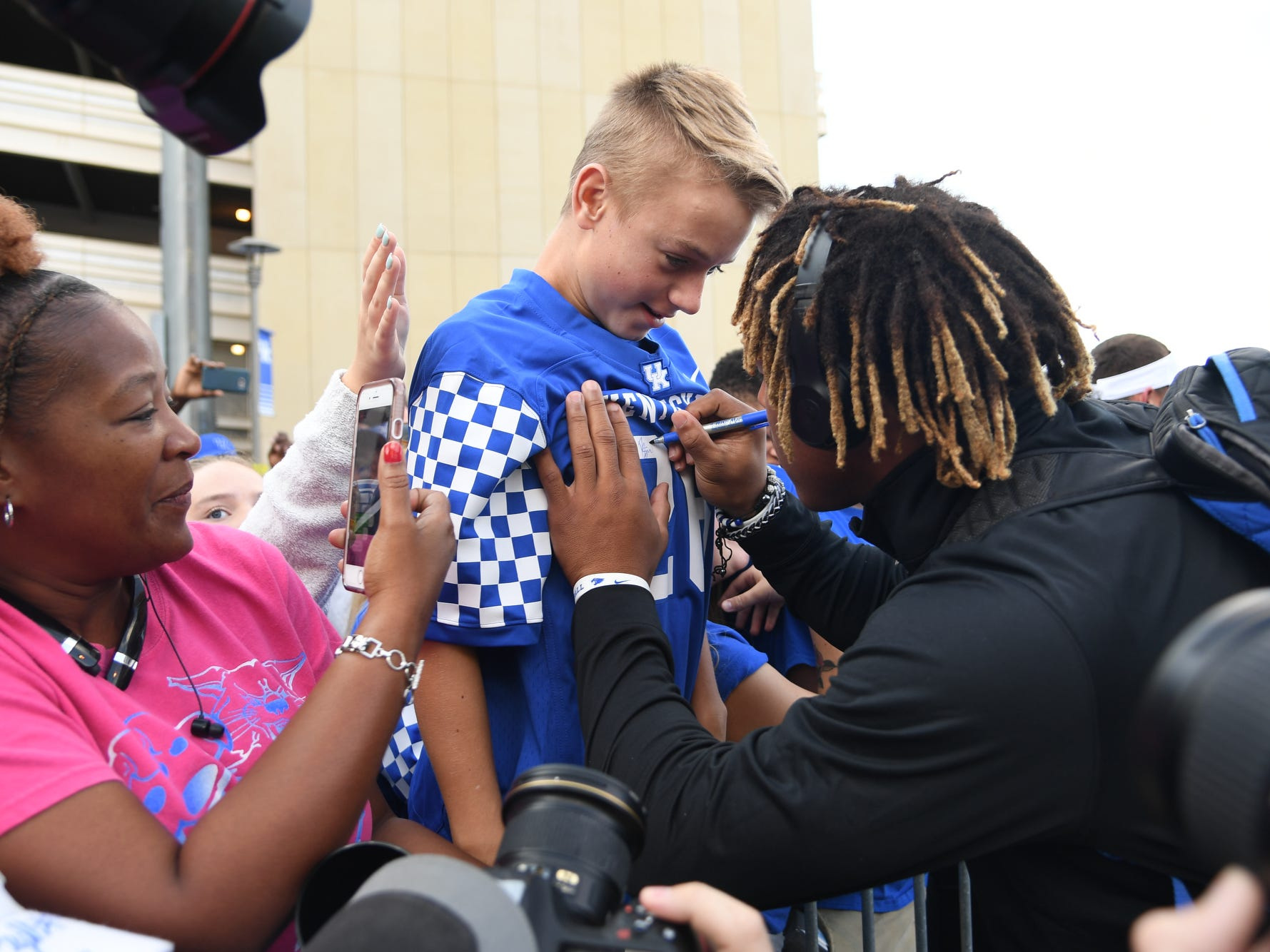 UK RB Benny Snell Jr. autographs a young fan's jersey during the Cat Walk before the University of Kentucky football game against South Carolina at Kroger Field in Lexington, Kentucky on Saturday, September 29, 2018.