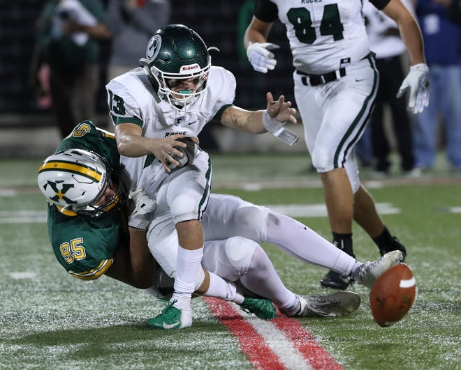 Trinity QB Bradley West (13) was sacked by St. X's Richard Bascom (95) as he coughed up the ball during their game at Cardinal Stadium.  Trinity recovered the loose ball.Sep. 28, 2018