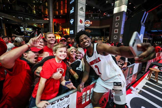 Louisville guard Darius Perry takes a photo with fans after the pep rally on Fourth Street Live!. The players interacted with the fans around the court, giving high fives and taking pictures as well. Sept. 28, 2018