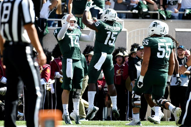 Michigan State's Brian Lewerke, left, celebrates his touchdown with LaÕDarius Jefferson during the second quarter on Saturday, Sept. 29, 2018, at Spartan Stadium in East Lansing.