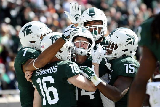 Brian Lewerke, center, celebrates his touchdown with teammates during the second quarter Saturday.