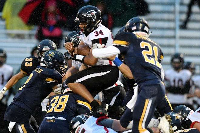 St. Johns' Jaymn Medlock, center, jumps over defenders for extra yards on a run during the first quarter on Friday, Sept. 28, 2018, in Haslett.