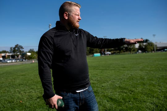 Michigan State alumnus Eric Mitchell, 28, talks about how he used to park on Munn Field for Spartans games while throwing the football on Munn Field on Saturday, Sept. 29, 2018, in East Lansing.