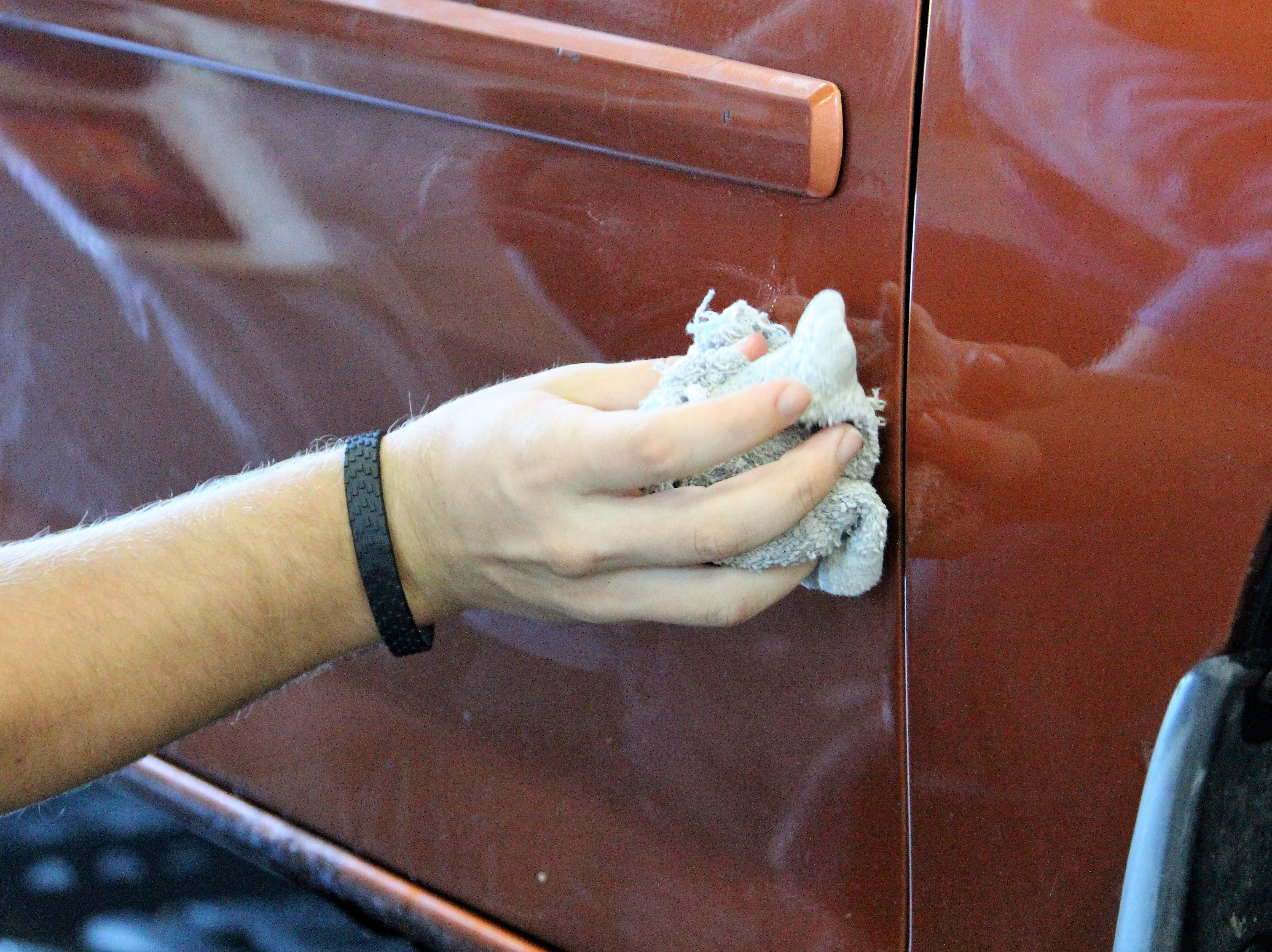 Damian Meyer applies a fresh layer of wax on Friday as he spent the morning detailing cars.