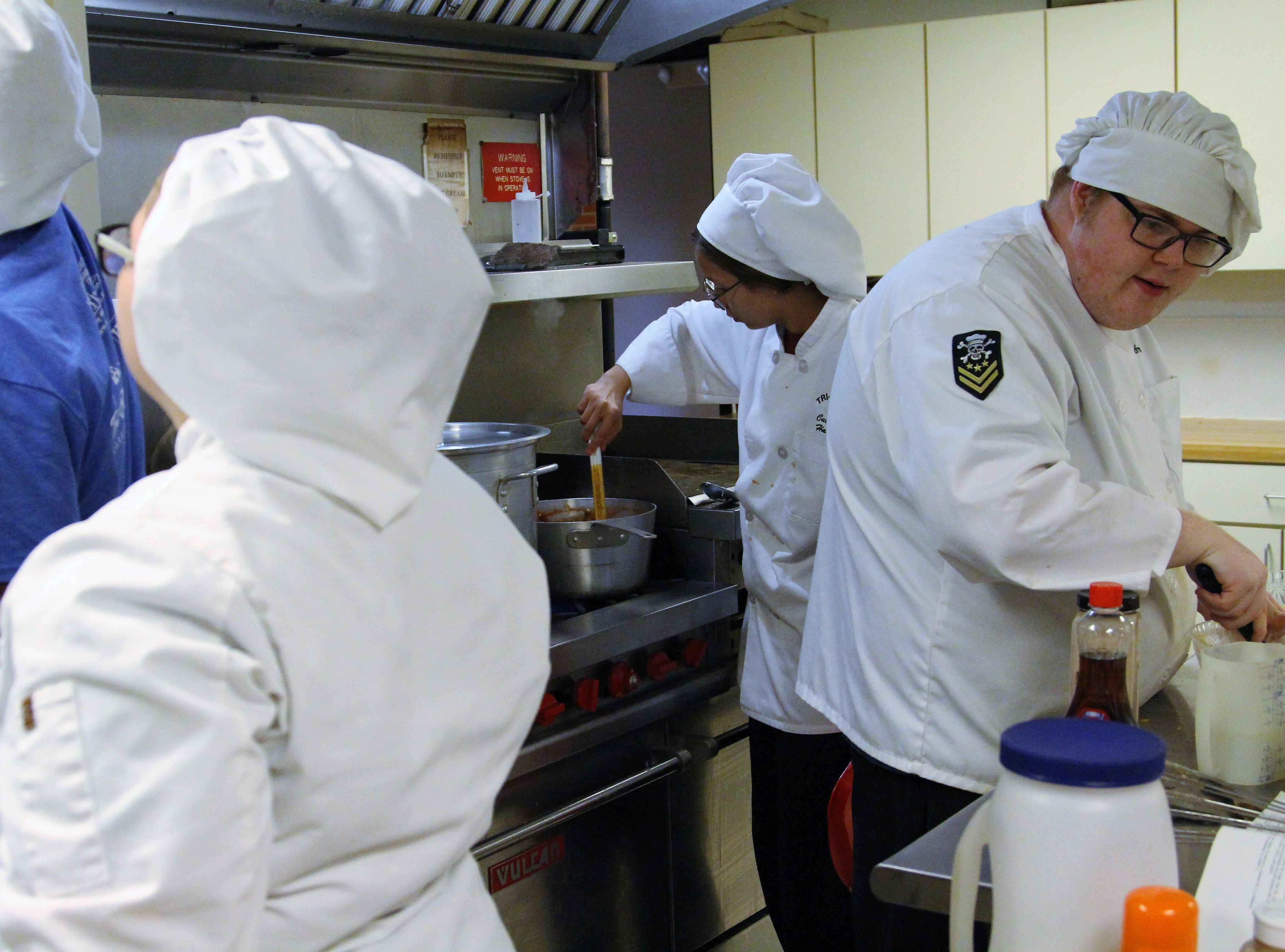 Culinary students navigate around each other in a busy kitchen at Salvation Army on Friday. They were cooking meals there as part of Make A Difference Day, a collaboration between Tri-Rivers Career Center and the United Way.