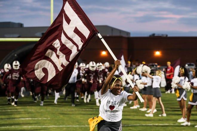 A cheerleader leads the Horn Lake football team onto the field.
