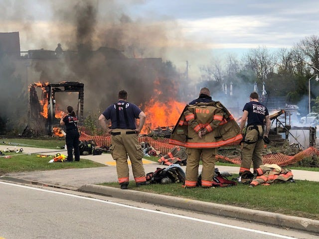 Firefighters look on as the first of two homes burns in a training exercise Saturday in Germantown.