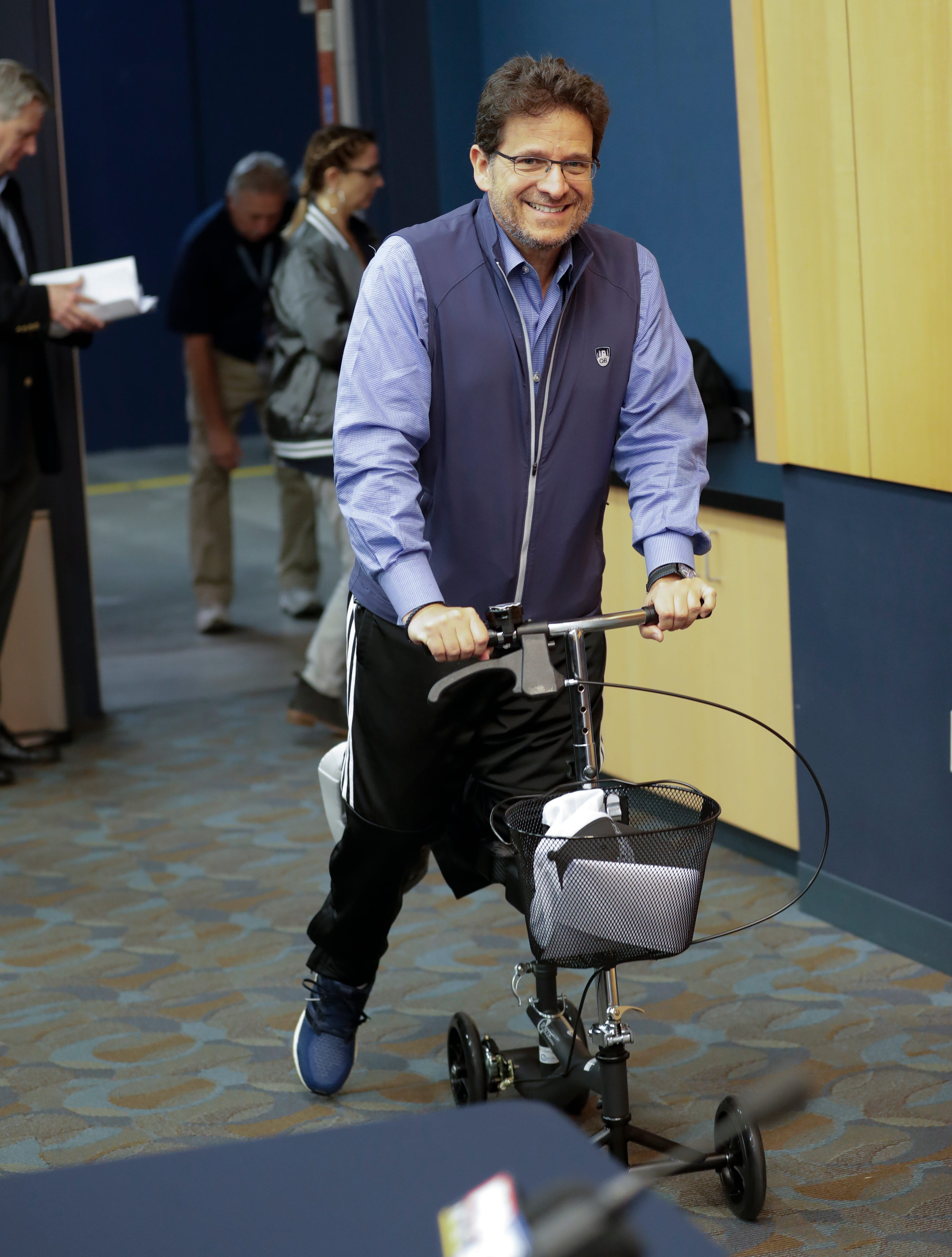 Milwaukee Brewers owner Mark Attanasio makes his way to a news conference Friday before a game between the Brewers and the Detroit Tigers. Attanasio is recovering from a torn left Achilles tendon.