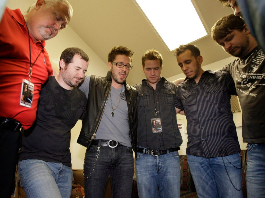 Former American Idol finalist Danny Gokey  prays with band members and mangers moments before he goes on stage at the Briggs and Stratton stage at Summerfest, Sunday, July 4, 2010 on the last day of Summerfest.