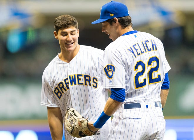 Christian Yelich greets his brother, Cameron, after he threw out the first pitch before the Brewers' game against the Tigers on Friday night at Miller Park.