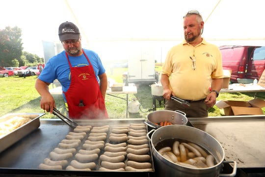 Dan Irwin, l, and Steve Feller of the Chester Lions cook Bratwurst during their annual Oktoberfest celebration at Chubb Park in Chester. September 29, 2018, Chester, NJ
