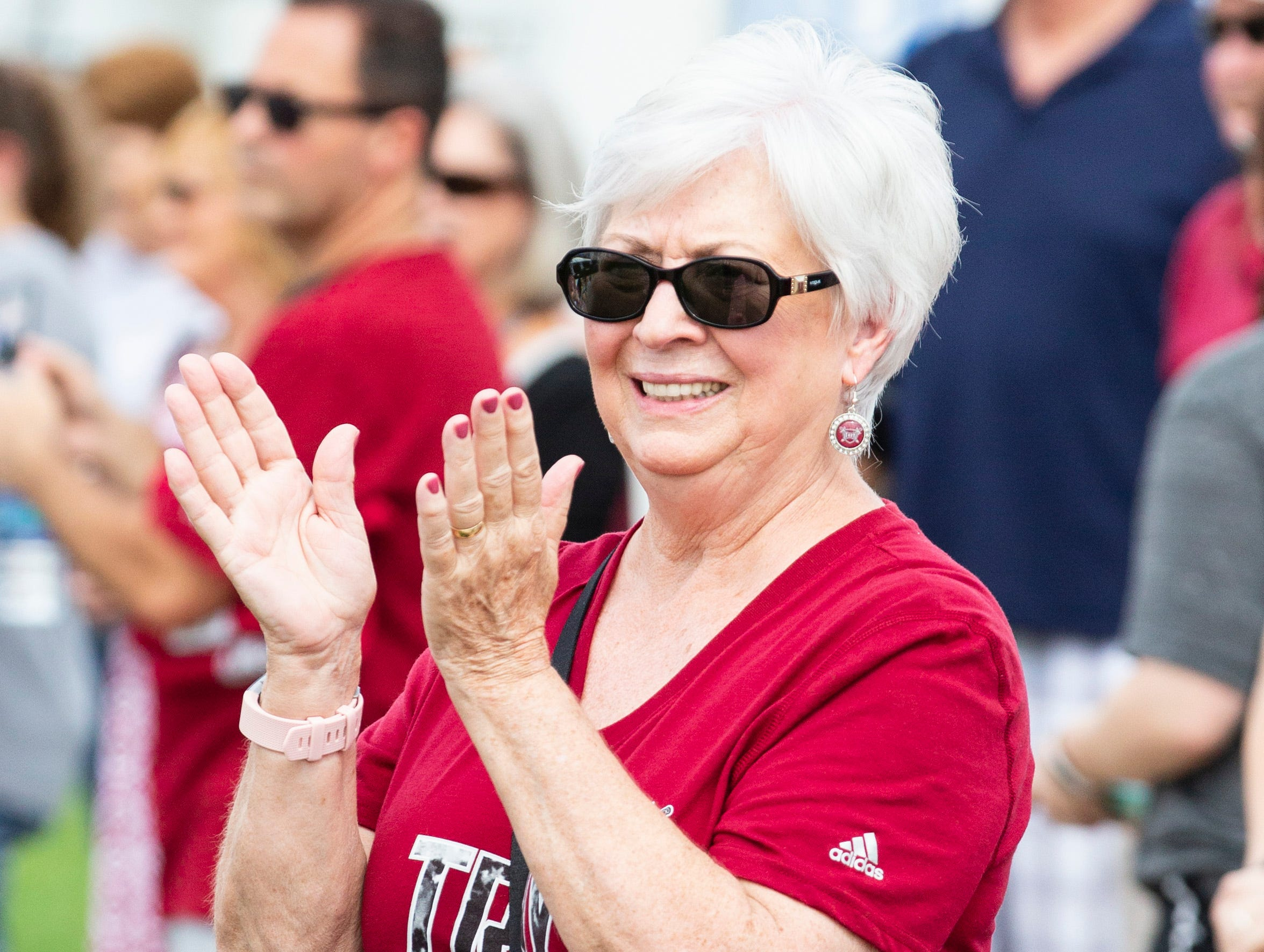 A Troy fan claps along to the band during a pep rally.