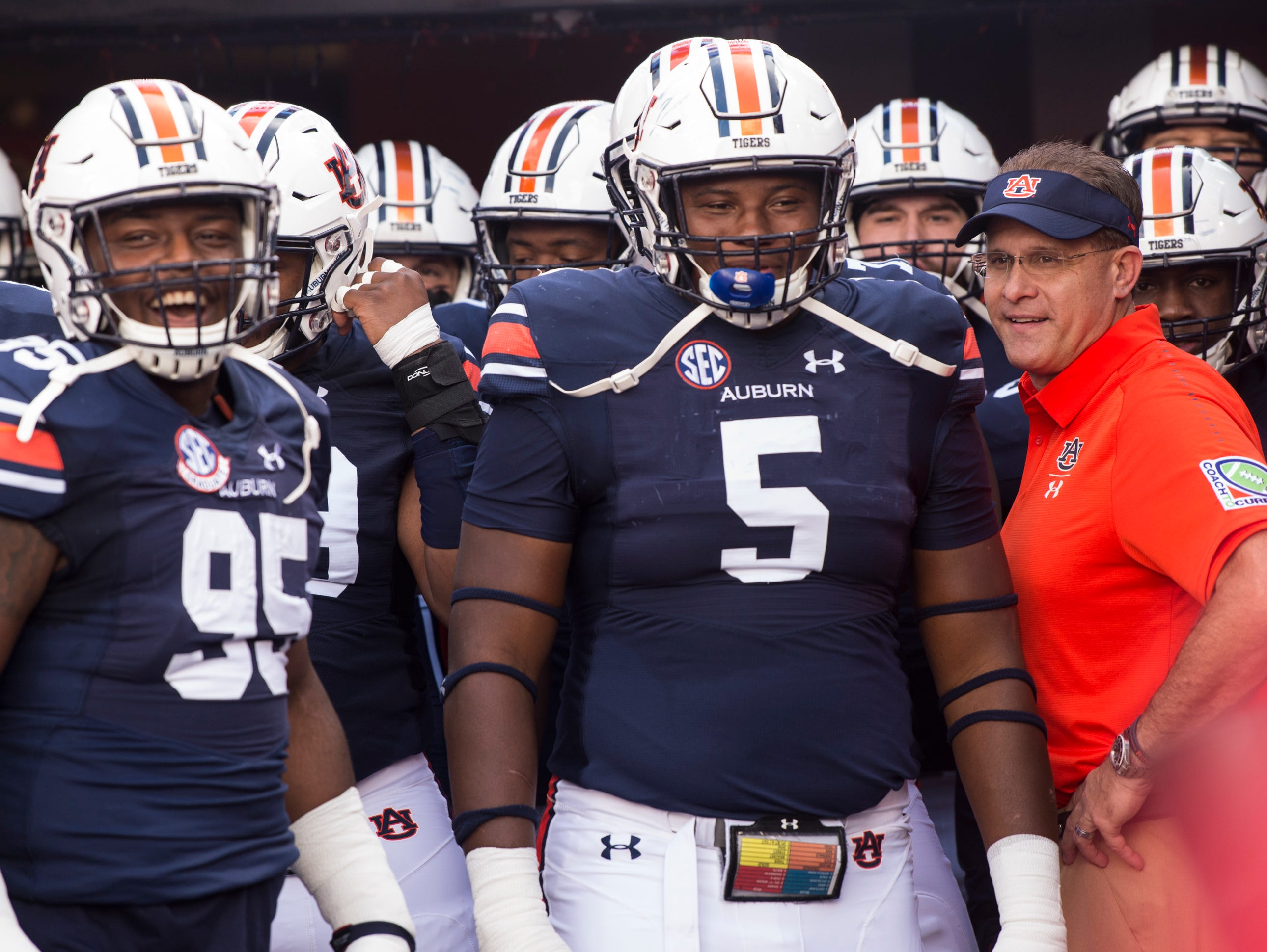 Auburn head coach Gus Malzahn, left, leads his team out on to the field at Jordan-Hare Stadium in Auburn, Ala., on Saturday, Sept. 29, 2018. Auburn leads Southern Miss 14-3, the game went into a weather delay with 4:27 left in the second quarter.