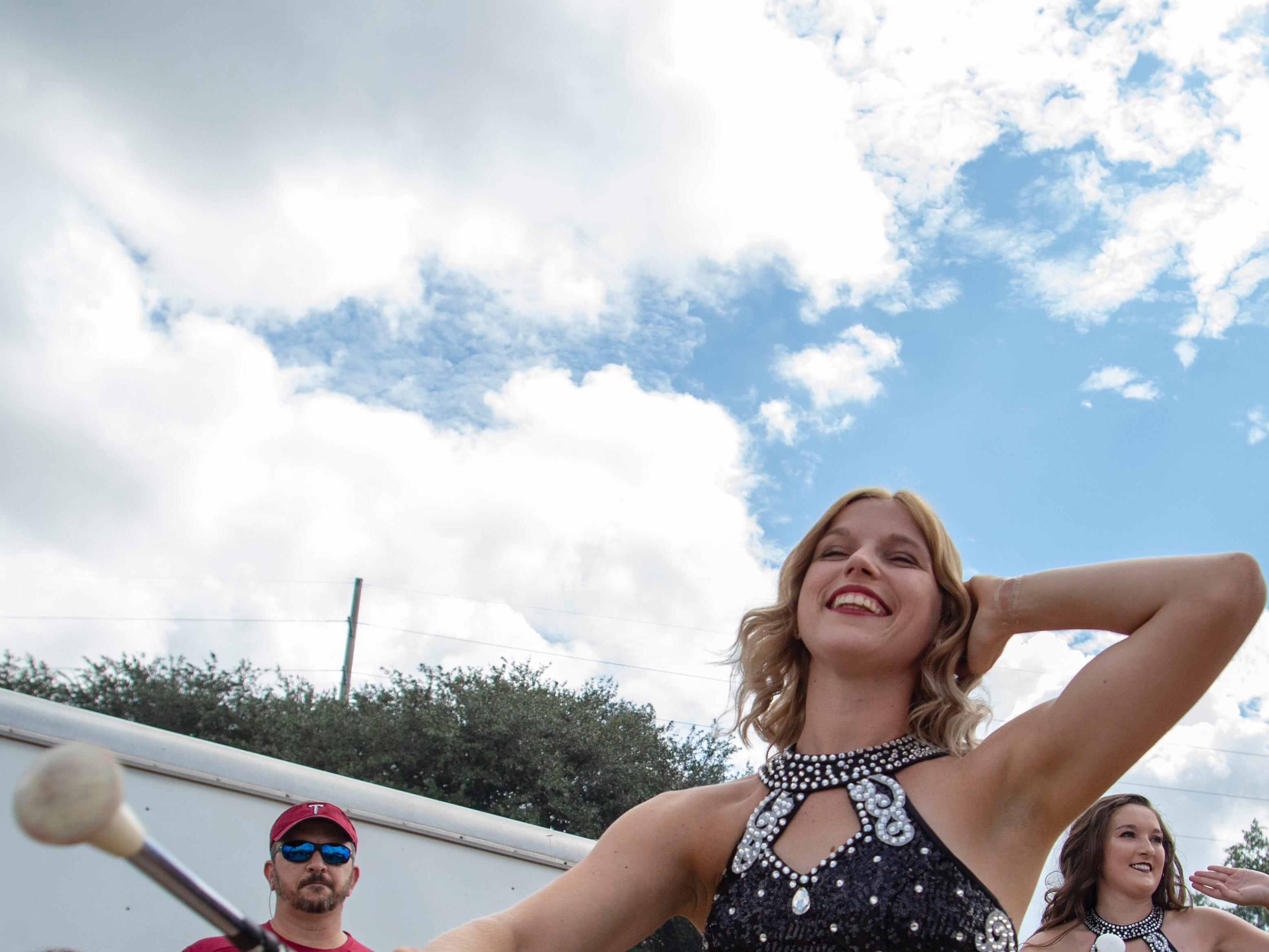 A Troy Majorette twirls her baton during Trojan Walk.