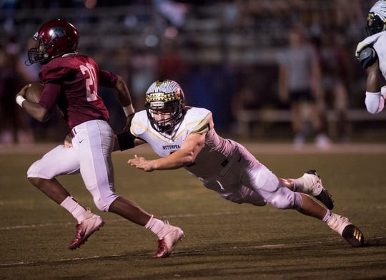 Wetumpka's Colton Adams (1) trips up Prattville's Keondre Powell (20) at Stanley-Jensen Stadium in Prattville, Ala., on Friday, Sept. 28, 2018. Prattville leads Wetumpka 17-14 at halftime.