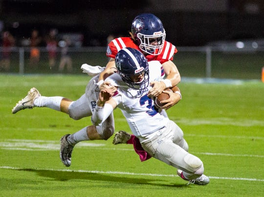 Academy's Daniel Lindsey is brought down by Trinity's Thomas Hargrove.