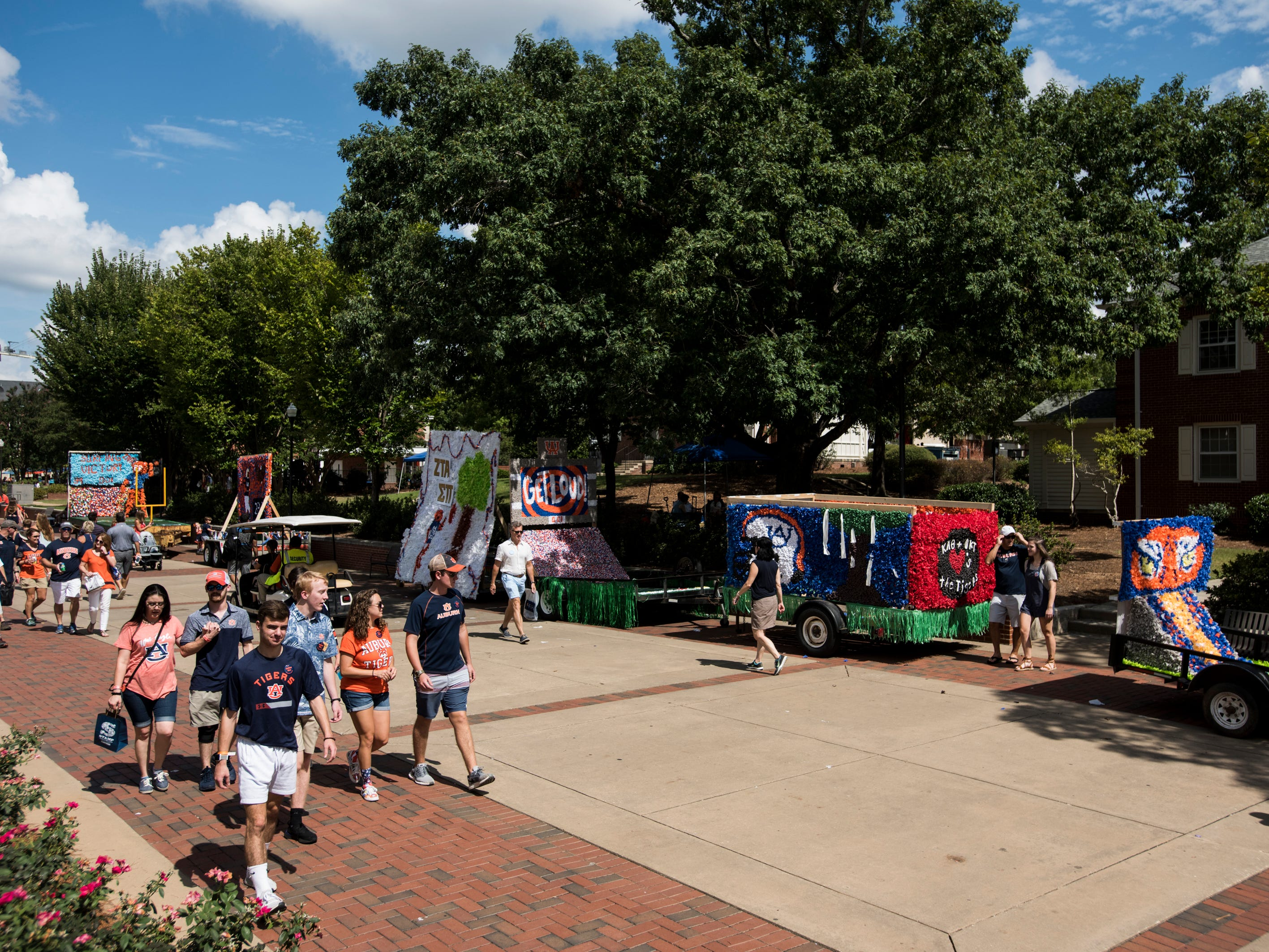 Fans walk by homecoming floats lined up on campus outside Jordan-Hare Stadium in Auburn, Ala., on Saturday, Sept. 29, 2018.