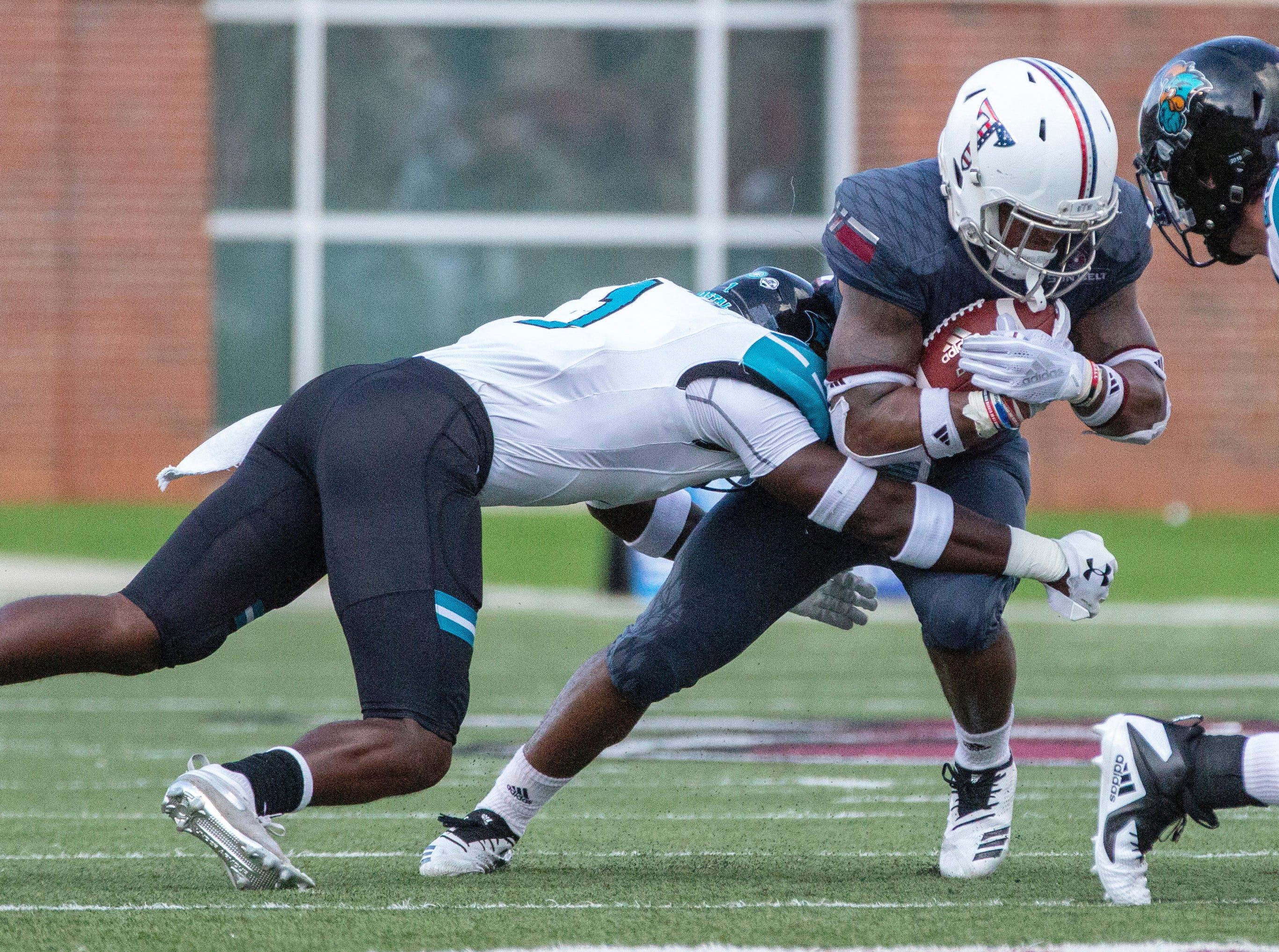 Coastal Carolina's Have Brown takes down Troy's Damion Willis during the third quarter.