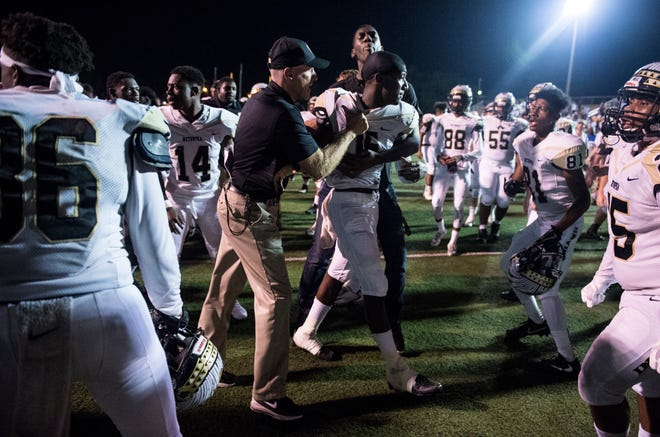 Wetumpka head coach Tim Perry pulls away one of his players as a shouting match breaks out between the two teams after the game at Stanley-Jensen Stadium in Prattville, Ala., on Friday, Sept. 28, 2018. Wetumpka defeats Prattville 49-23.