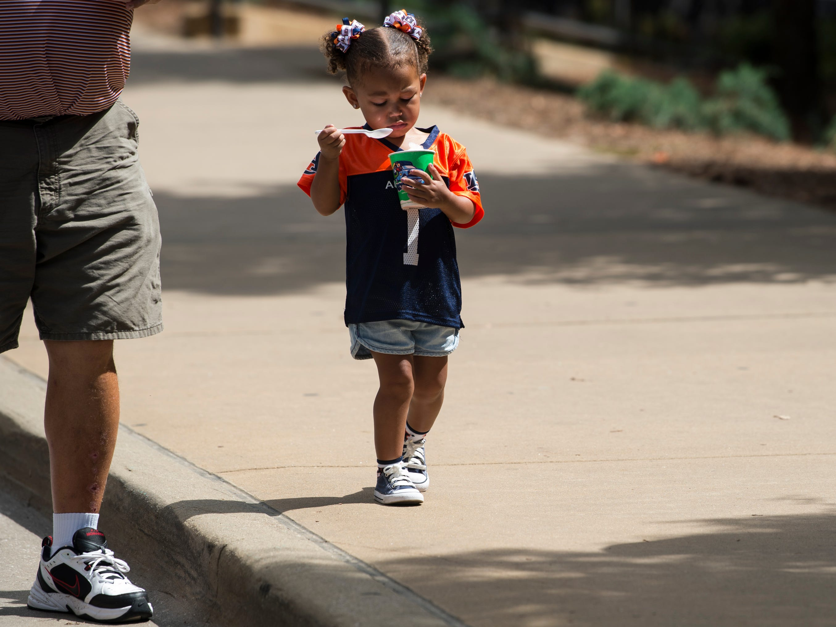 Ay'annah Favors, 2, enjoys a snowcone outside Jordan-Hare Stadium in Auburn, Ala., on Saturday, Sept. 29, 2018.