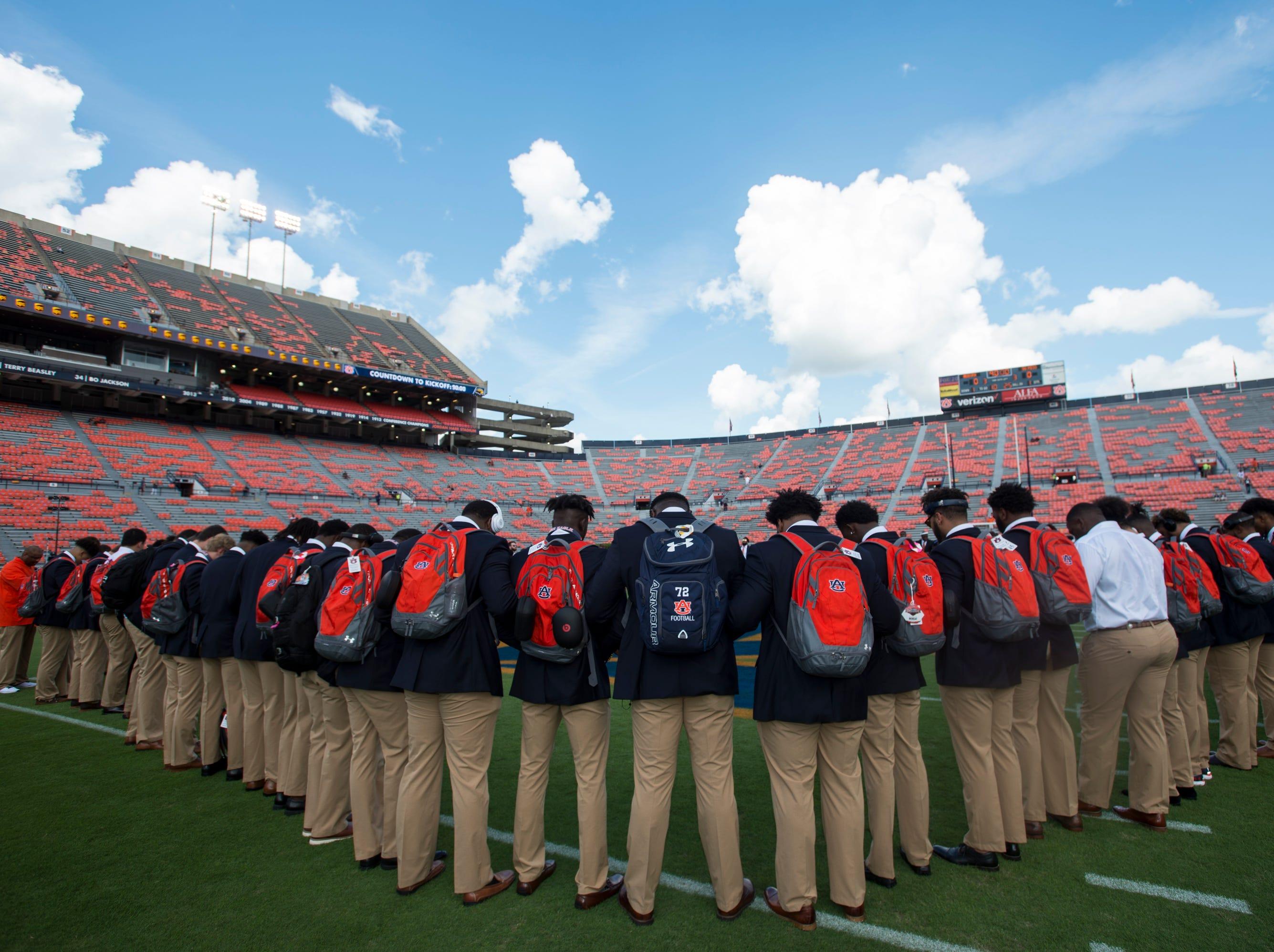 Auburn players huddle and pray on the field following the Tiger Walk at Jordan-Hare Stadium in Auburn, Ala., on Saturday, Sept. 29, 2018.