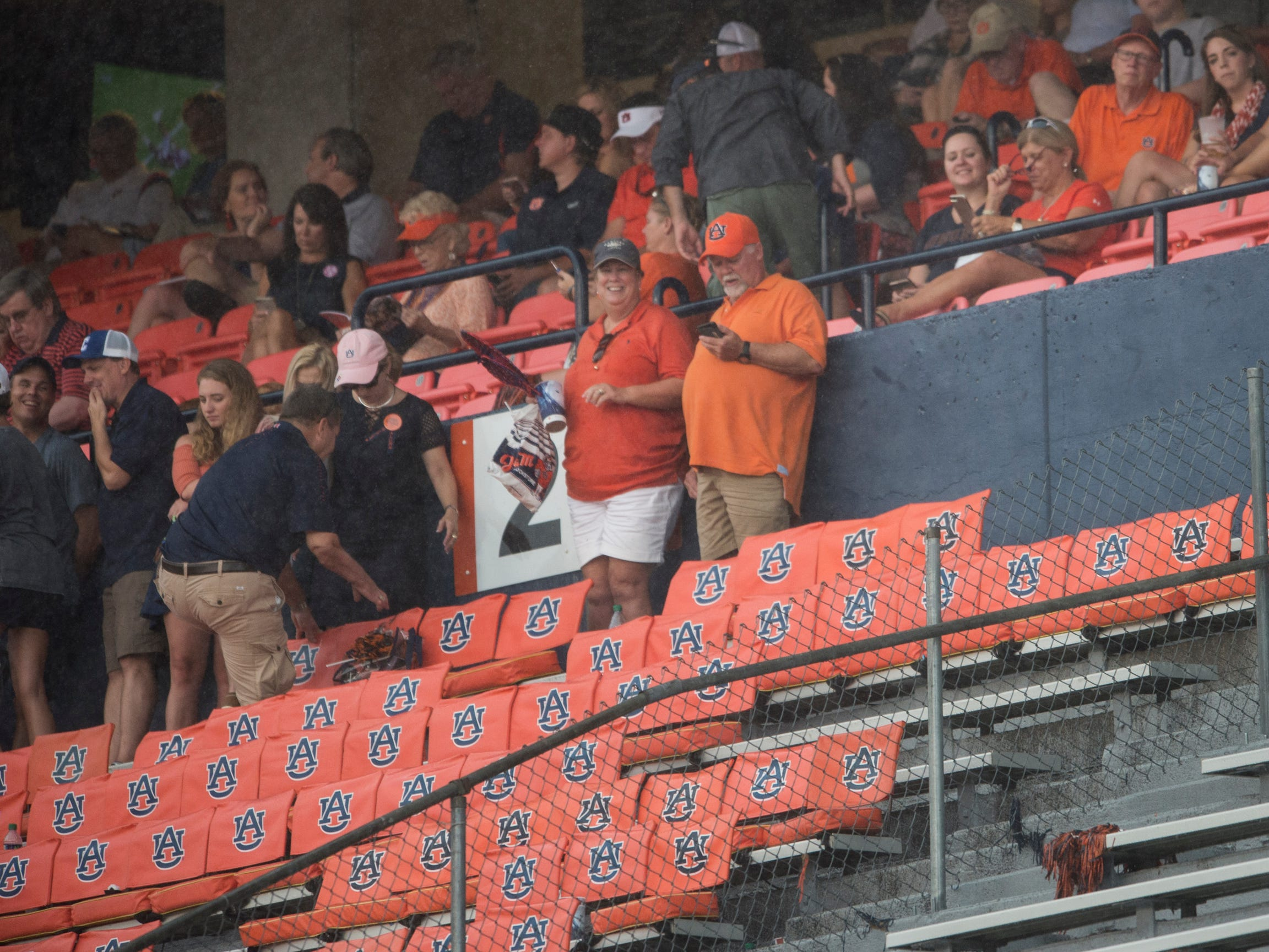 Fans get under cover during a weather delay at Jordan-Hare Stadium in Auburn, Ala., on Saturday, Sept. 29, 2018. Auburn leads Southern Miss 14-3, the game went into a weather delay with 4:27 left in the second quarter.