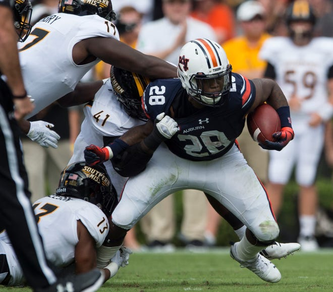 Auburn's JaTarvious Whitlow (28) struggles to evade a swarm of Southern Miss defenders at Jordan-Hare Stadium in Auburn, Ala., on Saturday, Sept. 29, 2018. Auburn leads Southern Miss 14-3, the game went into a weather delay with 4:27 left in the second quarter.