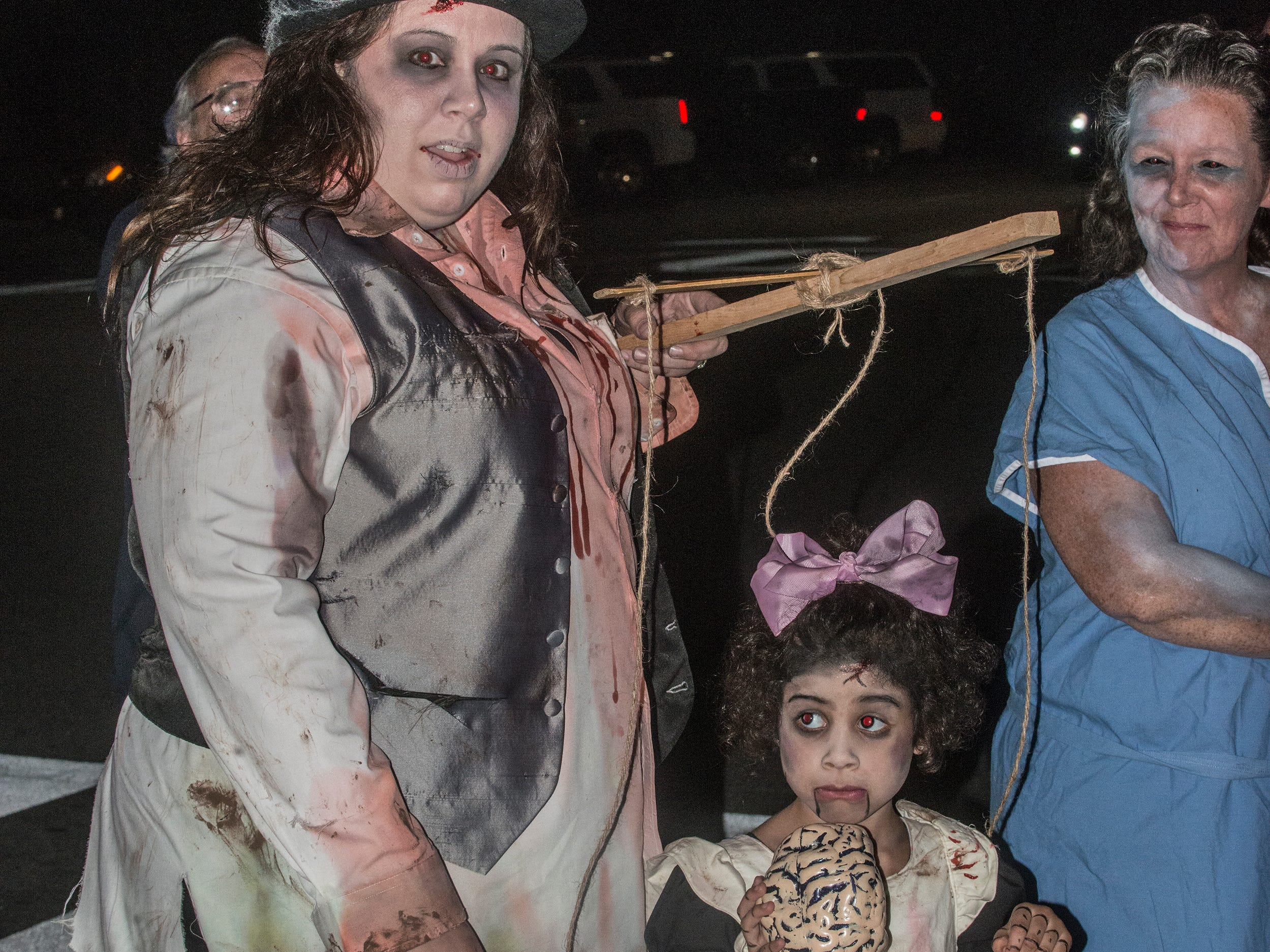 Samantha Legg with zombie puppet girl Alexiana, 4, who won the zombie princess award. There were many kinds of dead walking in downtown Montgomery on Friday, Sept. 28, 2018, for  Montgomery Zombie Walk and Prom, which collected food and money donations for the Montgomery Area Food Bank.